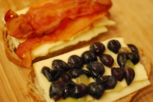 Bread, leaves, cheese, bacon on one side; bread cheese, grape halves on the other