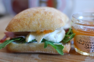 Ciabatta roll with a smear of ginger-cantaloupe jam, arugula, fresh mozz, and prosciutto. Lunch is served.